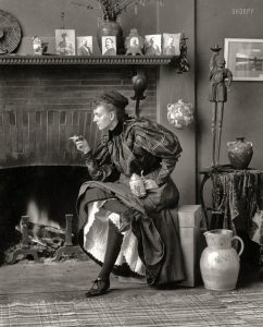 A picture of Frances Benjamin Johnston sitting on a stool. She is in a fancy period dress, but it is pulled up to show off her leg. She is smoking a cigarette, and holds a pitcher of beer in the other hand.