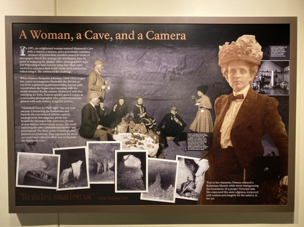 "A poster titles ""A woman, a cave, and a camera,"" with pictures and text. The text talks about Frances Benjamin Johnston, and the pictures include Johnston in period clothing, a picture of her crew consisting of four men and one woman, and several examples of her cave photography"