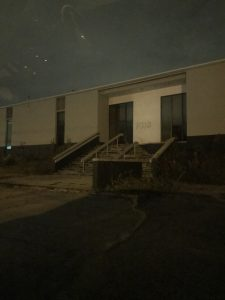PMC building entrance at night and after 16 years vacant with company name still on the main entrance.