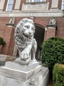 McMicken Hall lion, red brick building in background